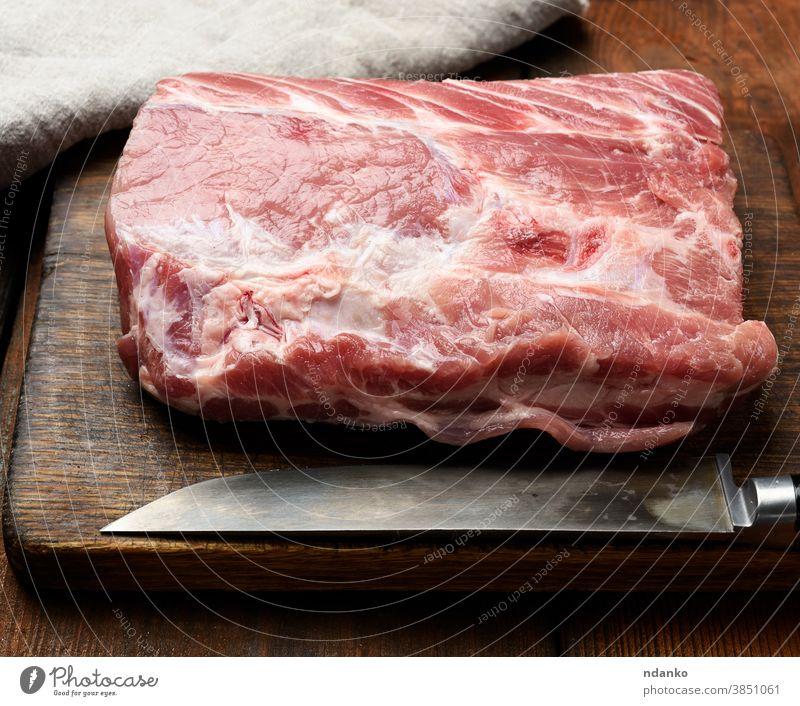 rohes Schweinefilet auf einem Holzschneidebrett Fleisch Serviette Ernährung Spielfigur Schweinefleisch Portion Vorbereitung Protein Lendenstück Holzplatte