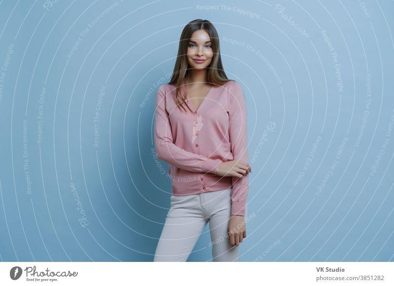 Modische brünette Kaukasierin in rosa Pullover und weißer Hose, geht zur Arbeit, schminkt sich, lächelt angenehm, isoliert auf blauem Hintergrund. Menschen, Stil, Lifestyle-Konzept