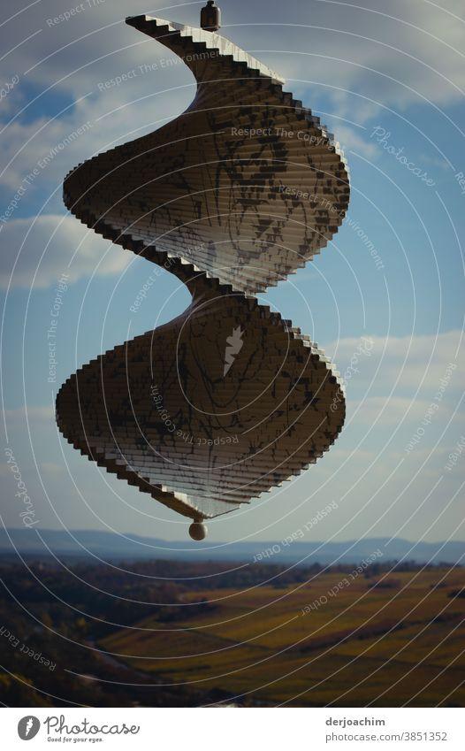Windspirale hängt an einer Befestigung . Blauer Himmel mit Wolken und der Horizont. Architektur windspirale Moderne Architektur Außenaufnahme Farbfoto modern
