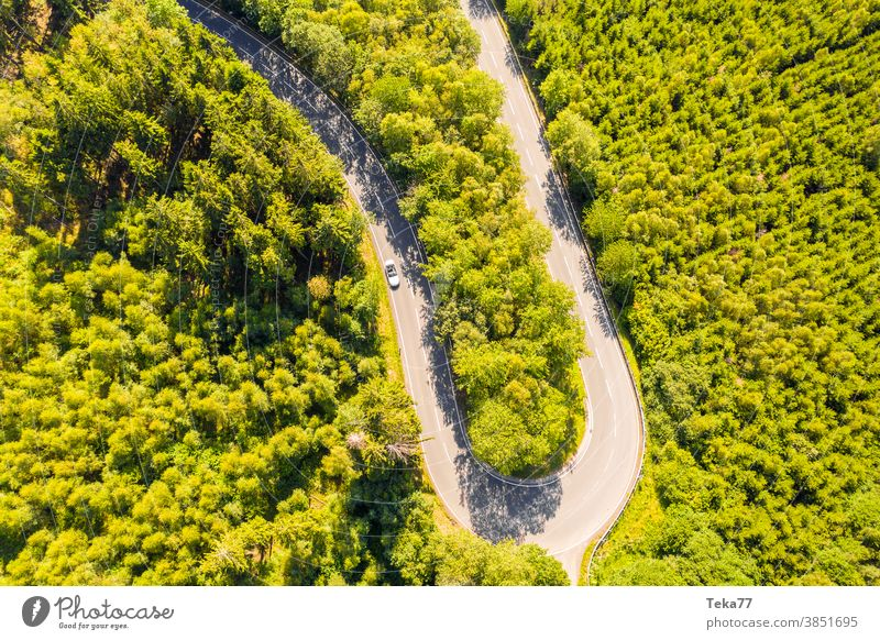 eine Waldstraßenkurve mit einem rasenden Auto von oben Straße kurvige Straße Wald von oben Straße von oben grün weiß weißes Cabrio PKW Bäume Baum