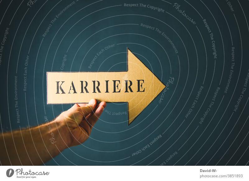 Karriere machen - Hand hält Pfeil mit Wort Richtungweisend Erfolg Ziel Business Zukunft ehrgeizig deuten richtungweisend vorwärts