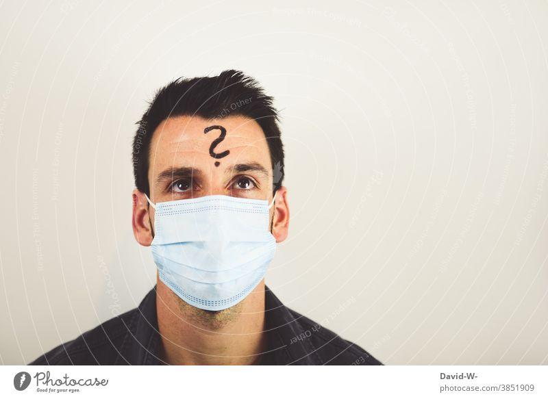 fragender Mann mit Atemschutzmaske / Mundschutz und Fragezeichen auf der Stirn Corona denken wieso ? nachdenklich skeptisch Zweifel pandemie Quarantäne