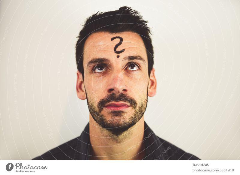 Mann mit Fragezeichen auf der Stirn nachdenklich ? denken nachdenken Fragender Blick unsicher Gedanken Zukunft
