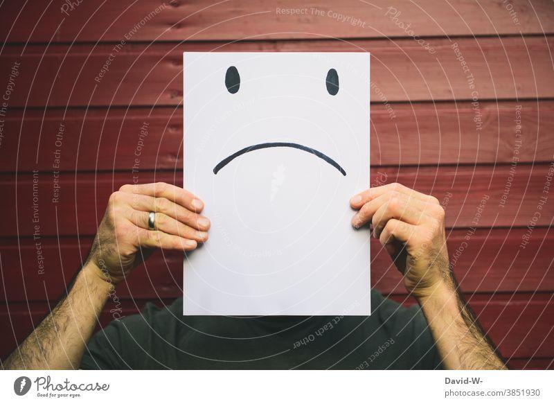 Mann mit trauriger Mimik aufgezeichnet - negativer smiley auf einem Zettel Gesicht Smiley Gesichtsausdruck böse Gefühle Emotionen verbittert Zeichung