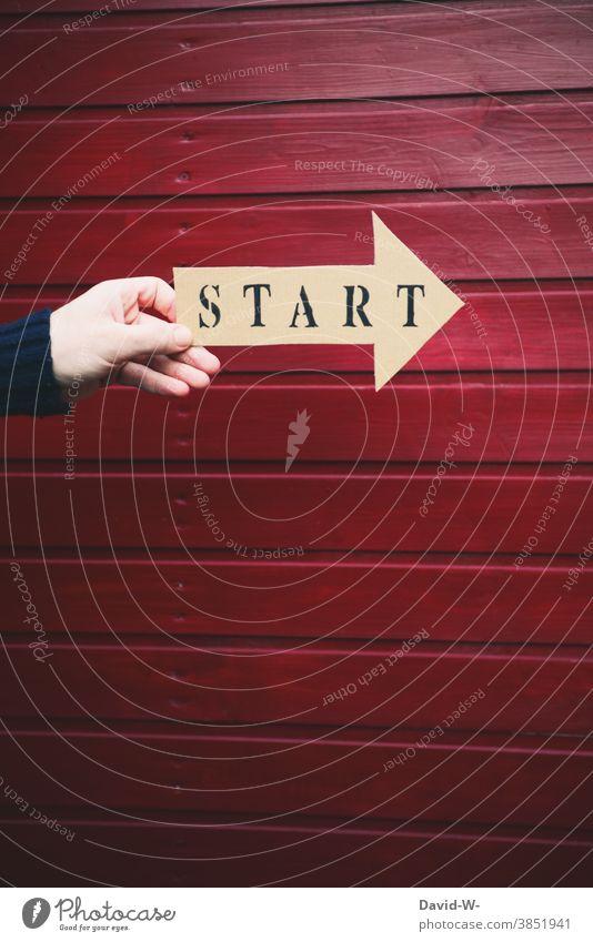 Start auf einem Pfeil aufgedruckt wird von einer Hand gehalten Beginn Los Anfang Zeichen Richtung Erfolg vorwärts Karriere