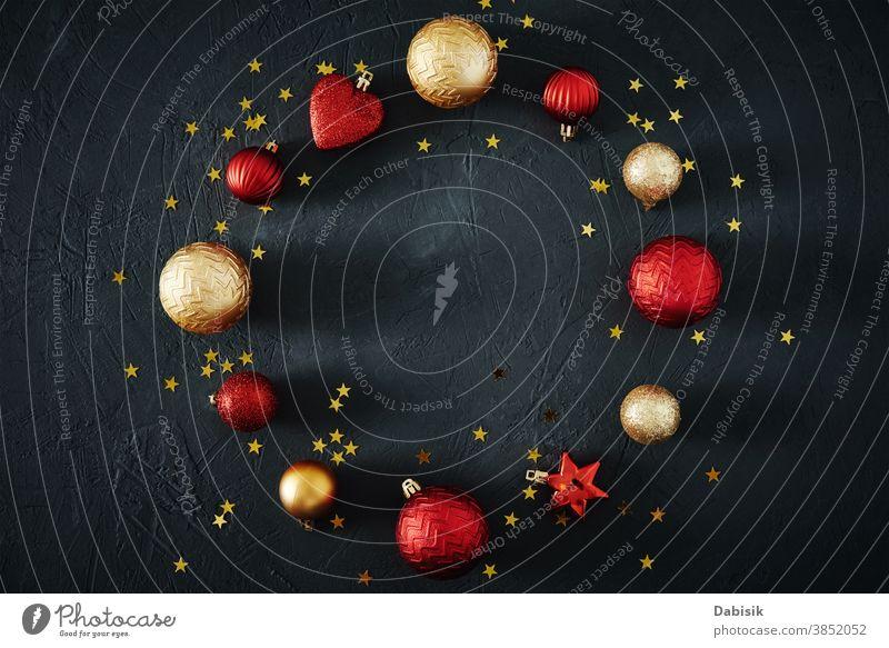 Weihnachtskomposition. Runder Rahmen aus roten und goldenen Weihnachtskugeln und festlichen Bändern auf dunklem Hintergrund, Draufsicht Weihnachten