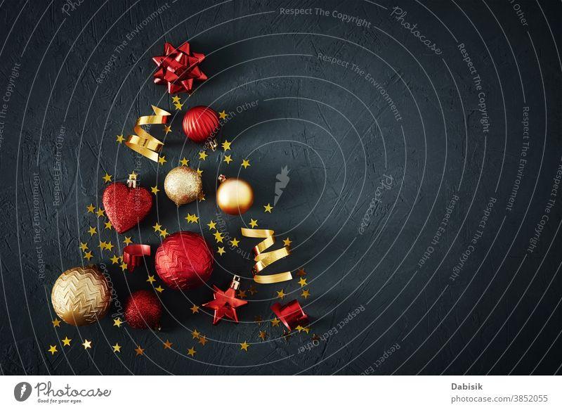 Weihnachtsbaum aus roten und goldenen Kugeln und festlichen Bändern auf dunklem Hintergrund mit Kopierfeld. Weihnachts-Konzept Weihnachten Baum