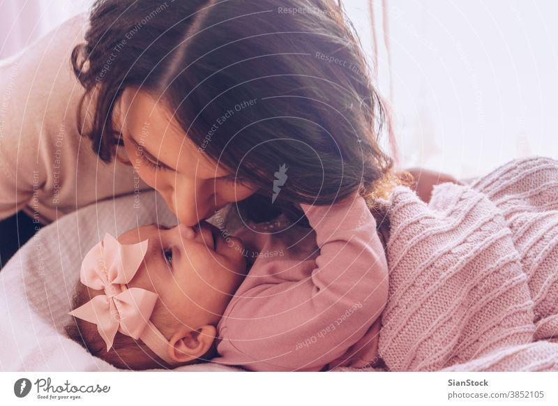 Junge Mutter küsst ihr bezauberndes Mädchen. Baby jung Mama Glück Familie Kind Nase Spielen Kuss Küssen liebevoll schön Porträt Fröhlichkeit Liebe Tochter wenig