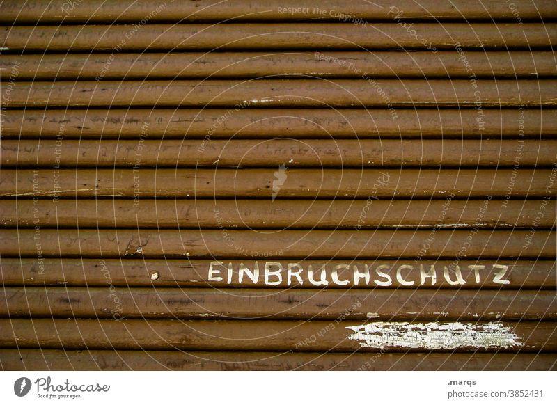 Einbruchschutz Rollladen Schriftzeichen geschlossen Ladengeschäft Einzelhandel Typographie Schutz Sicherheit braun Jalousie Nahaufnahme