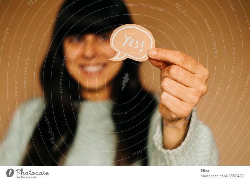 Frau hält eine Sprechblase auf der Yes steht. Zustimmung Freude Kommunikation Ja positiv Optimismus geschrieben Englisch Begeisterung Kommunizieren Ja sagen