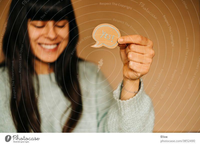 Lachende Frau hält eine Sprechblase auf der das Wort Ja in Englisch steht lachen positiv bejahen Freude gute Laune Erfolg erfolgreich Glücksgefühl Erfolg haben