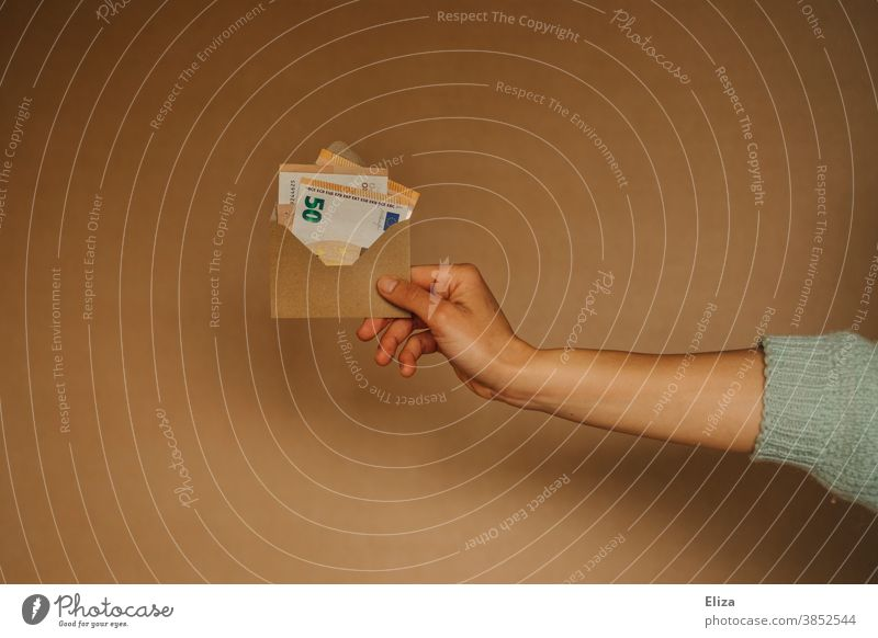 Hand hält einen Umschlag mit Geldscheinen. Konzept Finanzen, Rente, sparen, Geldgeschenk. Geschenk Rendite 50er Euro Bargeld Einkommen Bafög Kredit Geldsegen