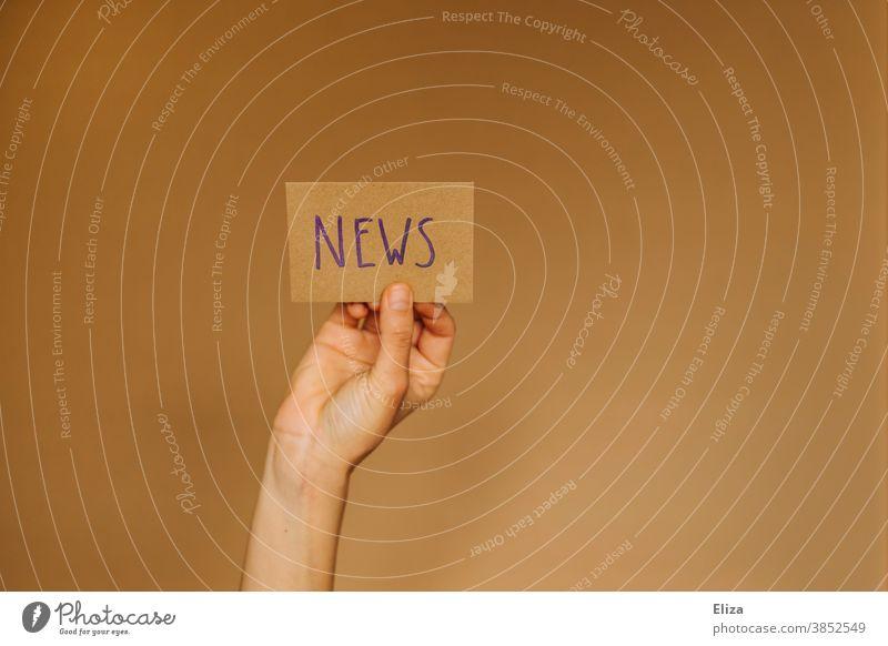 Hand hält ein Schild hoch auf dem News steht. Konzept Nachrichten, Newsletter, Neuigkeiten. englisch Information Journalismus Printmedien Medien Presse