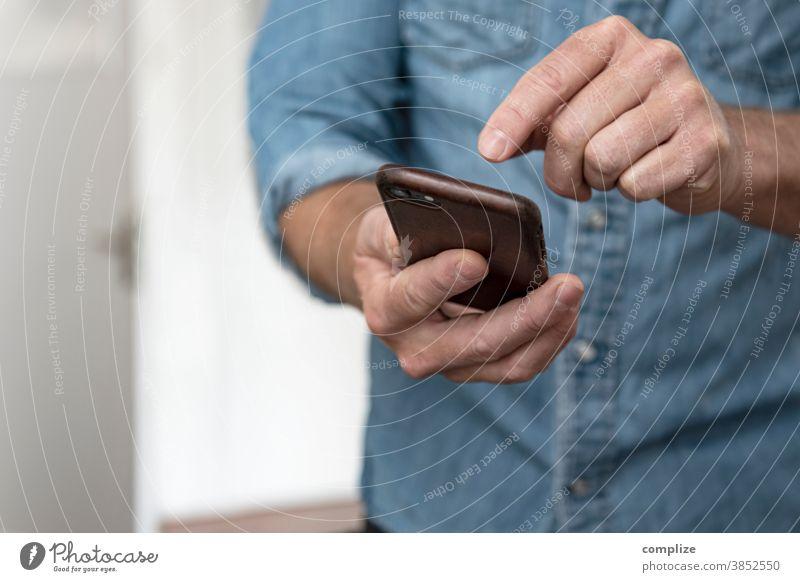 Mann tippt in sein Smartphone  - Smarthome Innenaufnahme Farbfoto Medien Tippen Telefongespräch Kommunizieren Homepage senden Internet Information SMS Handy