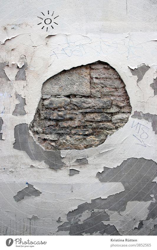 loch im putz einer wand mit blick auf die darunterliegenden ziegelsteine fassade mauer hauswand backsteine kaputt offen verputzt textur struktur hintergrund