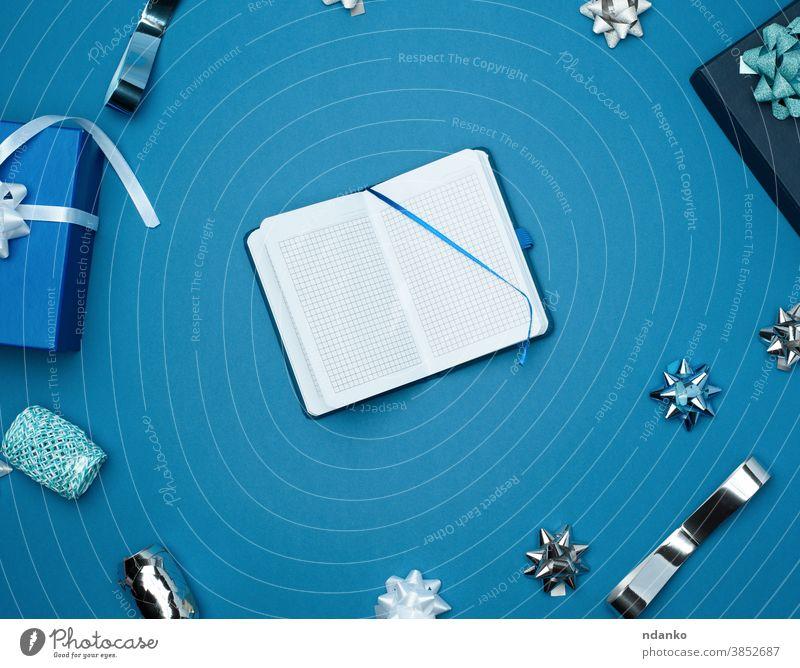 offenes Notizbuch mit leeren weißen Blättern, blauer Hintergrund mit Box Notizblock oben Jahrestag Geburtstag blanko Schleife Kasten Feier Weihnachten