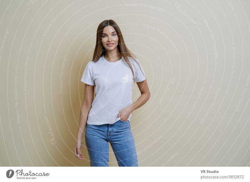 Studioaufnahme einer hübschen, schlanken Frau, die die Hand in der Tasche hält, lässiges T-Shirt und Jeans trägt, in entspannter Pose steht, selbstbewusst in die Kamera schaut, isoliert über beigen Hintergrund Gespräche mit dem Kunden führt