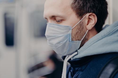 Nahaufnahme eines schweren Mannes, der an überfüllten Orten geht, zur Arbeit in die U-Bahn pendelt, eine medizinische Maske zum Schutz des Gesichts während des Ausbruchs und der Coronavirusinfektion trägt. Seuchenschutzkonzept