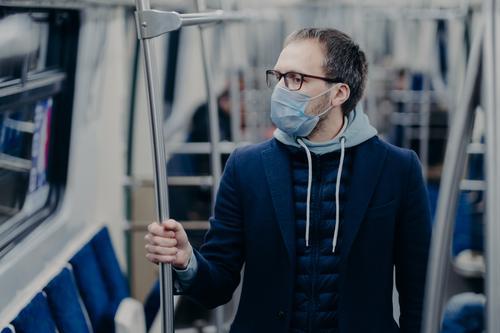 Prävention im öffentlichen Verkehr, Gesundheitsbewusstsein für den Pandemie-Schutz. Junger Mann trägt eine medizinische Maske, wenn er mit der S-Bahn reist, schützt sich vor Viren. Ausbruch von Covid-19 in Europa.