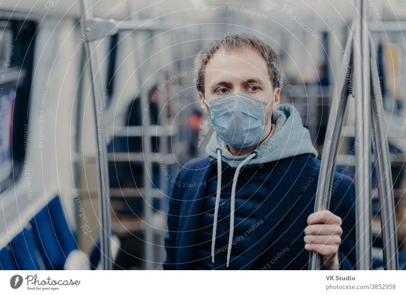 Foto eines männlichen Passagiers, der während einer U-Bahnfahrt während einer ansteckenden Krankheit eine Gesichtsmaske trägt, verhindert die Verbreitung des Coronavirus, posiert in öffentlichen Verkehrsmitteln, denkt über die Seuchensituation in seinem Land nach
