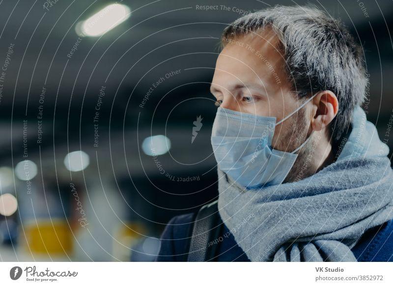 Nachdenklicher Mann trägt Schutzmaske gegen neues Coronavirus aus China, Schal um den Hals gewickelt, schaut irgendwo hin, denkt über die Seuchensituation nach. Grippe, Grippesymptome, Virus, Behandlungskonzept
