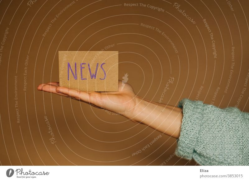 Eine Hand präsentiert ein Schild auf dem das Wort Nachrichten auf Englisch steht Berichterstattung Neuigkeiten Newsletter Journalismus Medien Information