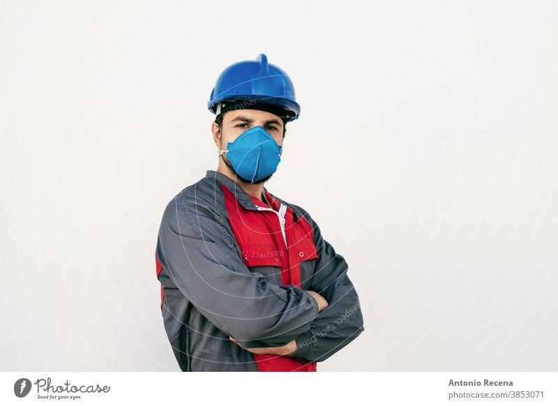 Attraktiver Arbeiter Mann mit Gesichtsmaske zum Schutz schaut in die Kamera covid-19 Mundschutz Uniform Sicherheit Pandemie Virus weißer Hintergrund Wand