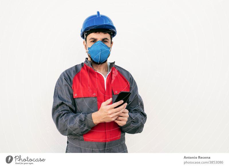 Bärtiger Arbeiter Mann mit Gesichtsmaske sieht Smartphone Telefon covid-19 Mundschutz Uniform Sicherheit Pandemie Virus weißer Hintergrund Wand Coronavirus