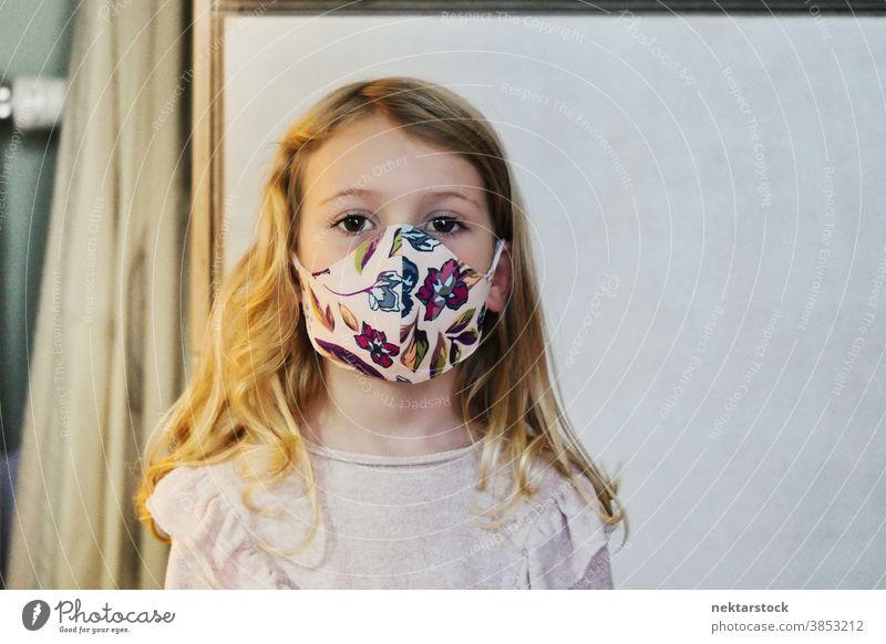 Blondes Mädchen mit schützender Gesichtsmaske Kind Porträt Mundschutz Gesichtsschutzmaske blond Kaukasier Lifestyle Frau in die Kamera schauen im Innenbereich