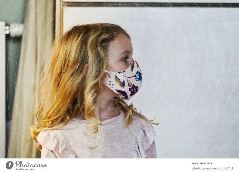Profil eines blonden weiblichen Kindes mit schützender Gesichtsmaske Mädchen Porträt Mundschutz Gesichtsschutzmaske Kaukasier Lifestyle Frau Wegsehen