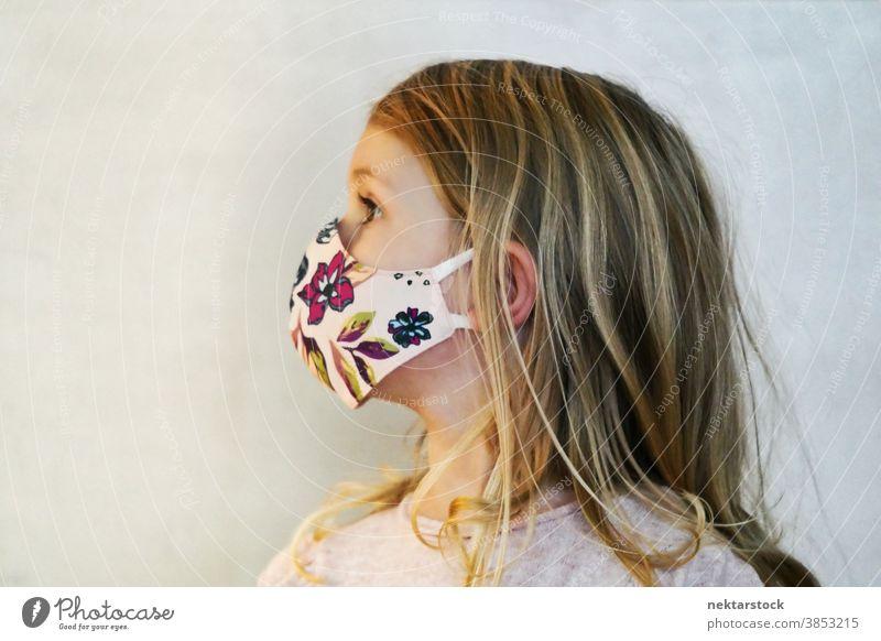 Profil blondes Mädchen mit Schutzmaske Kind Porträt Mundschutz Gesichtsschutzmaske Kaukasier Lifestyle Frau Wegsehen Kopf gedreht im Innenbereich