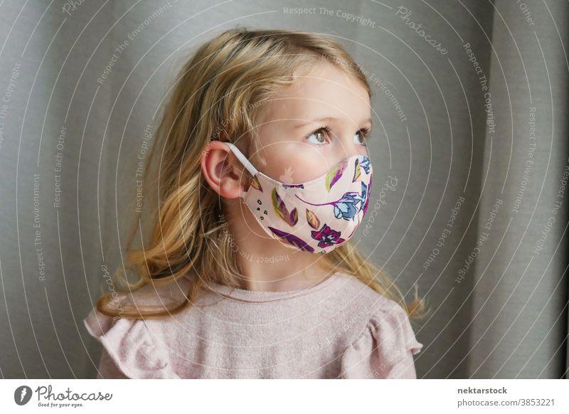 Kaukasisches Mädchen mit schützender Gesichtsmaske schaut weg Kind Porträt Mundschutz Gesichtsschutzmaske blond Kaukasier Lifestyle Seitenansicht Frau Wegsehen