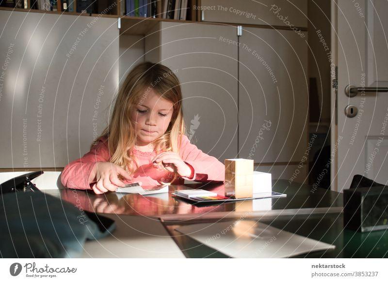 Kaukasisches Mädchen spielt in der Halle am Tisch Kind spielen blond Kaukasier Lifestyle Frau im Innenbereich natürliche Beleuchtung wachsen lernen