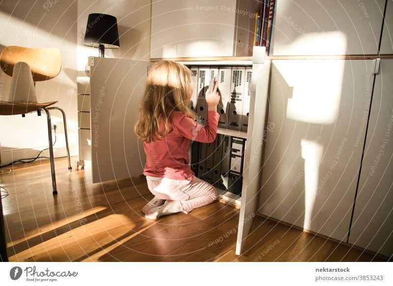 Kniendes Kind schaut auf Dokumentenordner im Schrank Mädchen spielen blond Kaukasier Lifestyle Kleiderschrank Mappe Ordner Schriftstück Rückansicht umgedreht
