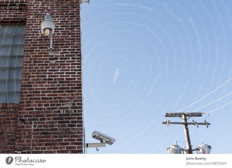 Sicherheitskamera, Stromleitungen und Industrielicht am Lagergebäude aus Backstein Überwachungskamera großer Bruder überwachen Monitor Fotokamera Video