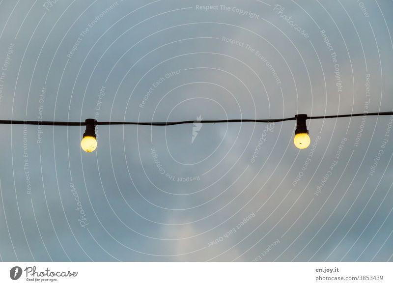 zwei leuchtende Glühbirnen hängen an einem Seil unter freiem Himmel mit Wolken Licht Lichter Beleuchtung Lampen Energie Abend Strom Dämmerung