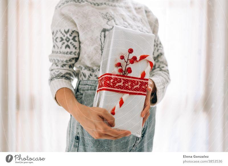 Junge, nicht wiedererkennbare Frau hält in einem Geschenkkarton aus Metallpapier mit rotem Zwirn und Süßigkeiten. Weihnachts-Silvester-Geschenk. Weihnachten