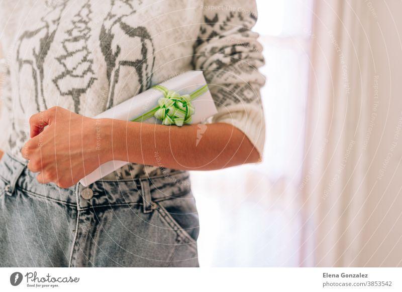 Junge, nicht wiedererkennbare Frau hält in einem Geschenkkarton aus weißem Papier mit grünem Zwirn. Weihnachts-Silvester-Geschenk. Weihnachten Frohe Weihnachten