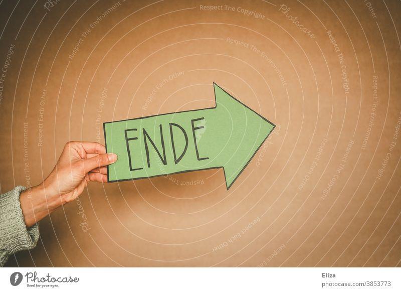 Hand hält einen grünen Pfeil auf dem das Wort Ende geschrieben steht. Trennung, aus, vorbei. Vergänglichkeit vergangen Schild pfeil Richtung Orientierung Ausweg