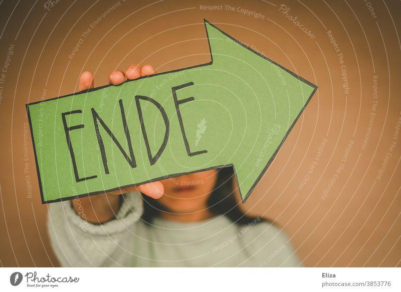 Frau hält einen grünen Pfeil auf dem Ende geschrieben steht endend Endlichkeit vorbei aus zuende Vergänglichkeit Trennung vergangen neutraler Hintergrund