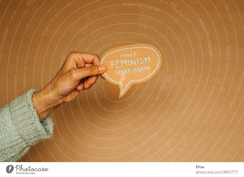 """Hand hält eine Sprechblase auf der """"Make feminism great again"""" steht. Feminismus, Emanzipation, Gleichberechtigung. Gleichstellung Gesellschaft (Soziologie)"""