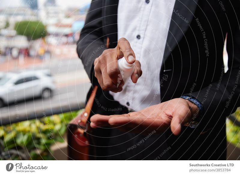 Nahaufnahme eines Geschäftsmannes, der während einer Gesundheitspandemie seine Hände mit Desinfektionsmitteln besprüht Business Büro Arbeiter