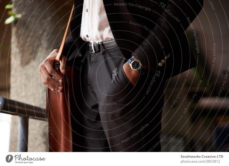 Nahaufnahme eines Geschäftsmannes mit einer Ledertasche, der mit der Hand in der Tasche steht Business Büro Arbeiter abschließen Stehen im Freien Hand-in-Tasche