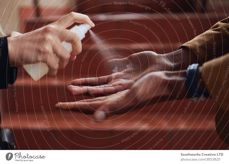 Nahaufnahme eines Geschäftsmannes, dessen Hände während einer Gesundheitspandemie mit Sanitizer besprüht wurden Business Büro Arbeiter Desinfektionsmittel