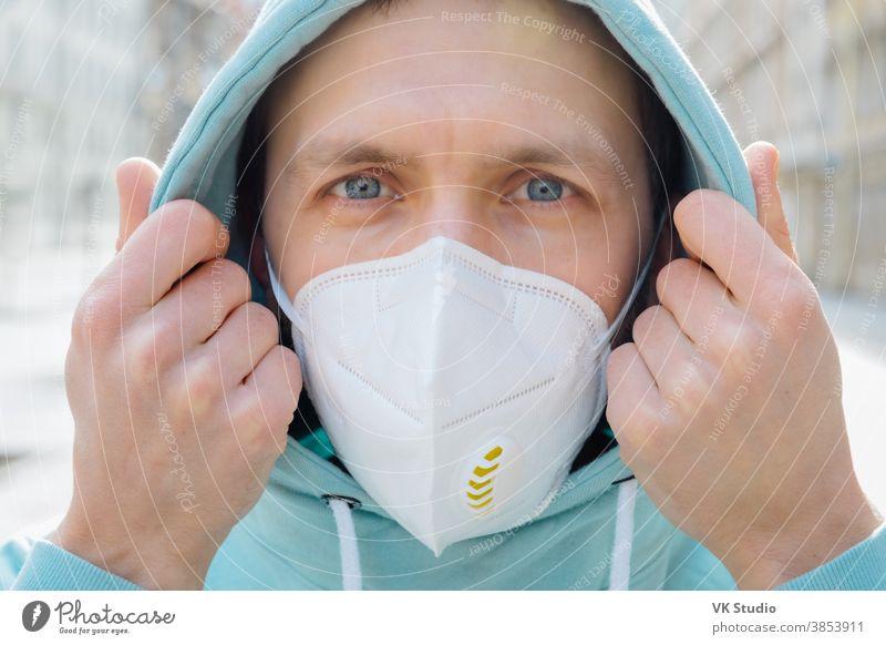 Nahaufnahme eines europäischen Mannes, der sein Gesicht mit einer Atemschutzmaske schützt, Kapuzenpulli trägt, draußen auf der Straße posiert, ernsthaft in die Kamera schaut, verhindert Coronavirus oder Covid-19, Grippe. Straße während der Quarantäne