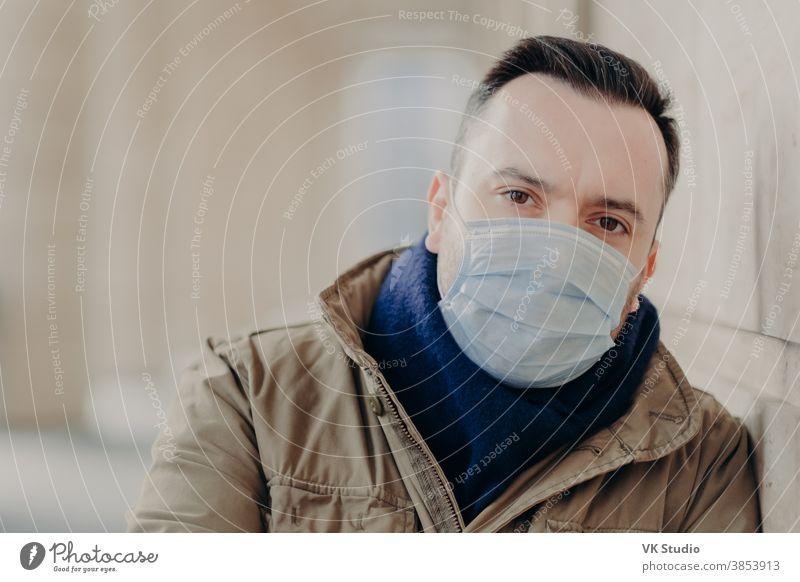 Freiluftaufnahme eines jungen europäischen Mannes mit Coronavirus-Symptomen, trägt schützende Operationsmaske, versucht sich vor Viren und Infektionen zu schützen, muss zum Arzt. Problem der Straßen- und Luftverschmutzung