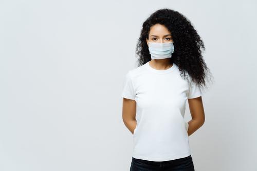 Halbe Aufnahme einer Afroamerikanerin, die sich in Selbstisolierung oder Quarantäne befindet, trägt während des Coronavirus-Ausbruchs eine medizinische Maske, hört Nachrichten, versucht, das Virus nicht zu verbreiten, bleibt lange zu Hause