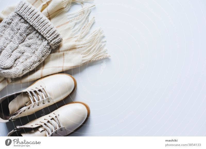 Wintermode-Set Draufsicht. Konzept des Online-Shoppings. Schuhe, Strickmütze und Schal in neutralen Beige-Tönen auf weißem Hintergrund Mode Kleidung Accessoire