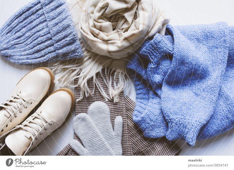 stilvolle, moderne Winter- oder Herbstkleidung für Frauen von oben betrachtet. Trendige Schuhe, Pullover und Accessoires in Beige- und Blautönen mit Weihnachtsbeleuchtung und Herbstlaub.