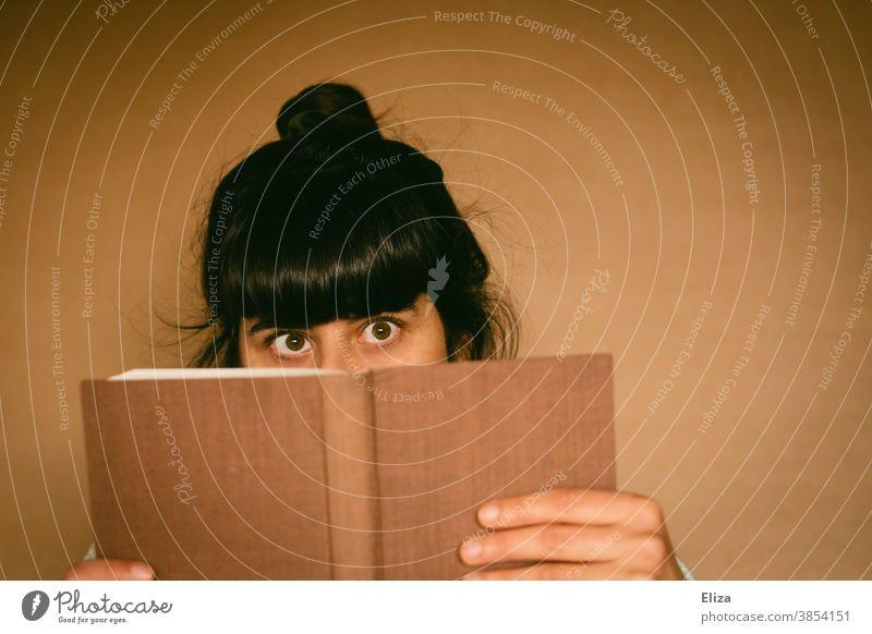 Junge Frau schielt hinter einem Buch hervor lesen schielen ertappt lustig Lesestoff neugierig Roman Printmedien Literatur junge Frau brünett
